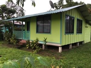 small green Caribbean house on stilts